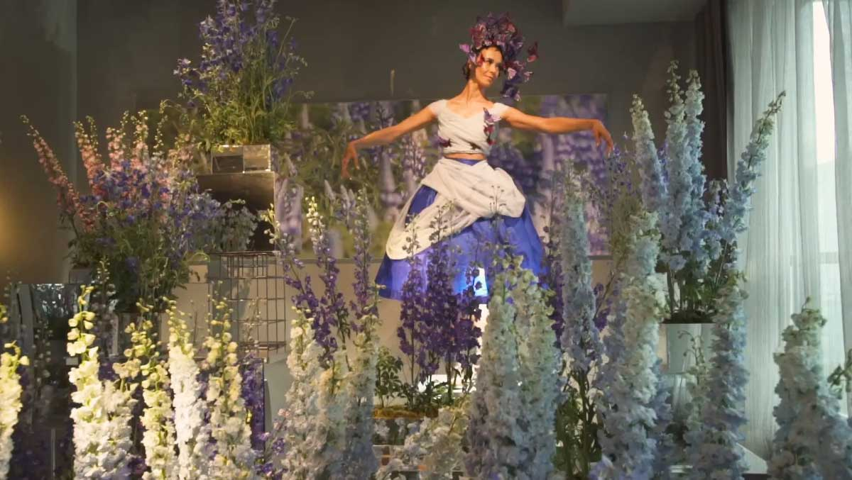 Dancer surrounded by floral display.