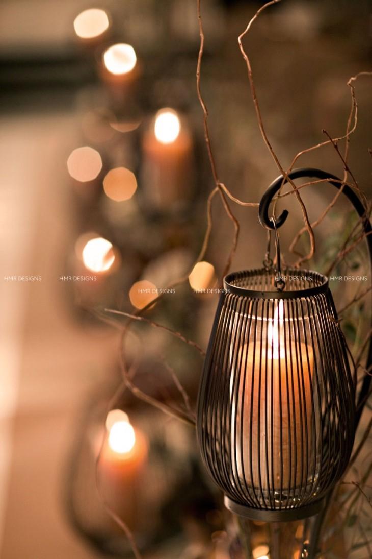 A lantern warms an aisle at an autumn wedding by HMR Designs