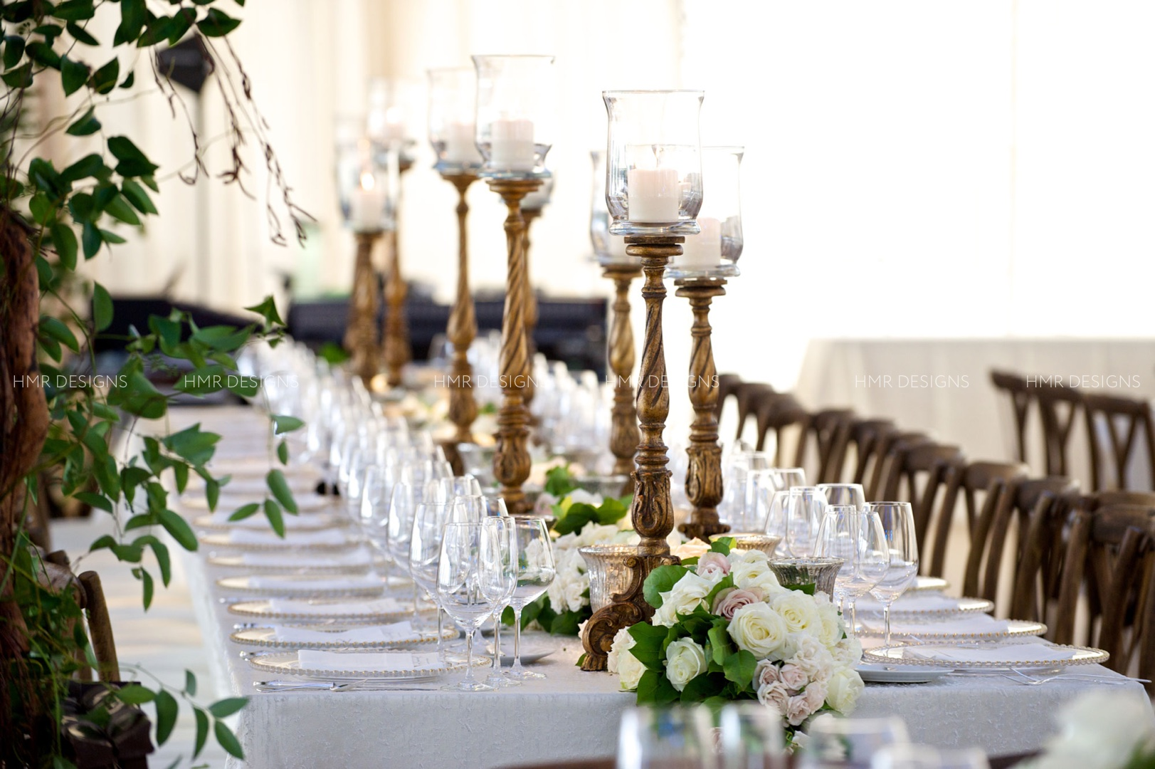 Gold candlesticks, greenery and roses line the long tables of a tented summer wedding by HMR Designs