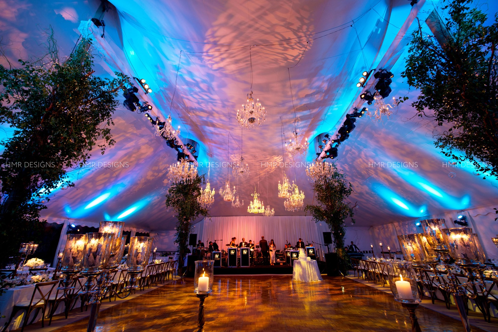Greenery in the shape of trees covers tent poles for a wedding lit by chandeliers and projections by HMR Designs