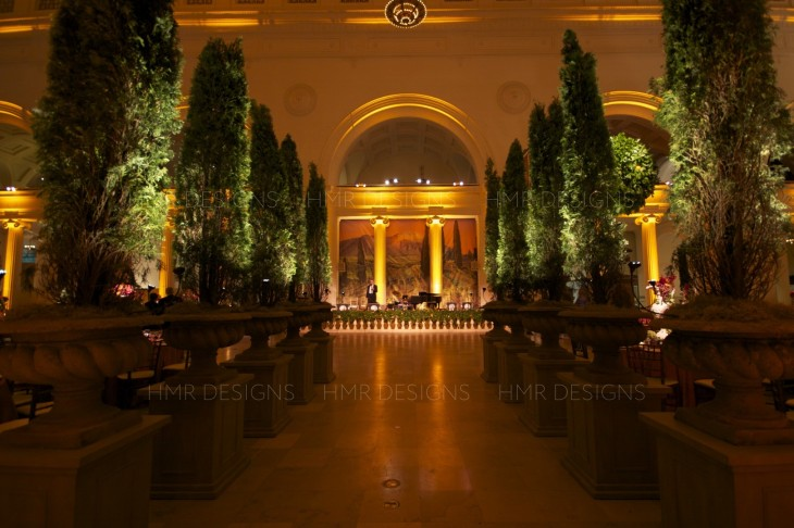 Rows of trees line an aisle at the Field Museum with floral by HMR Designs
