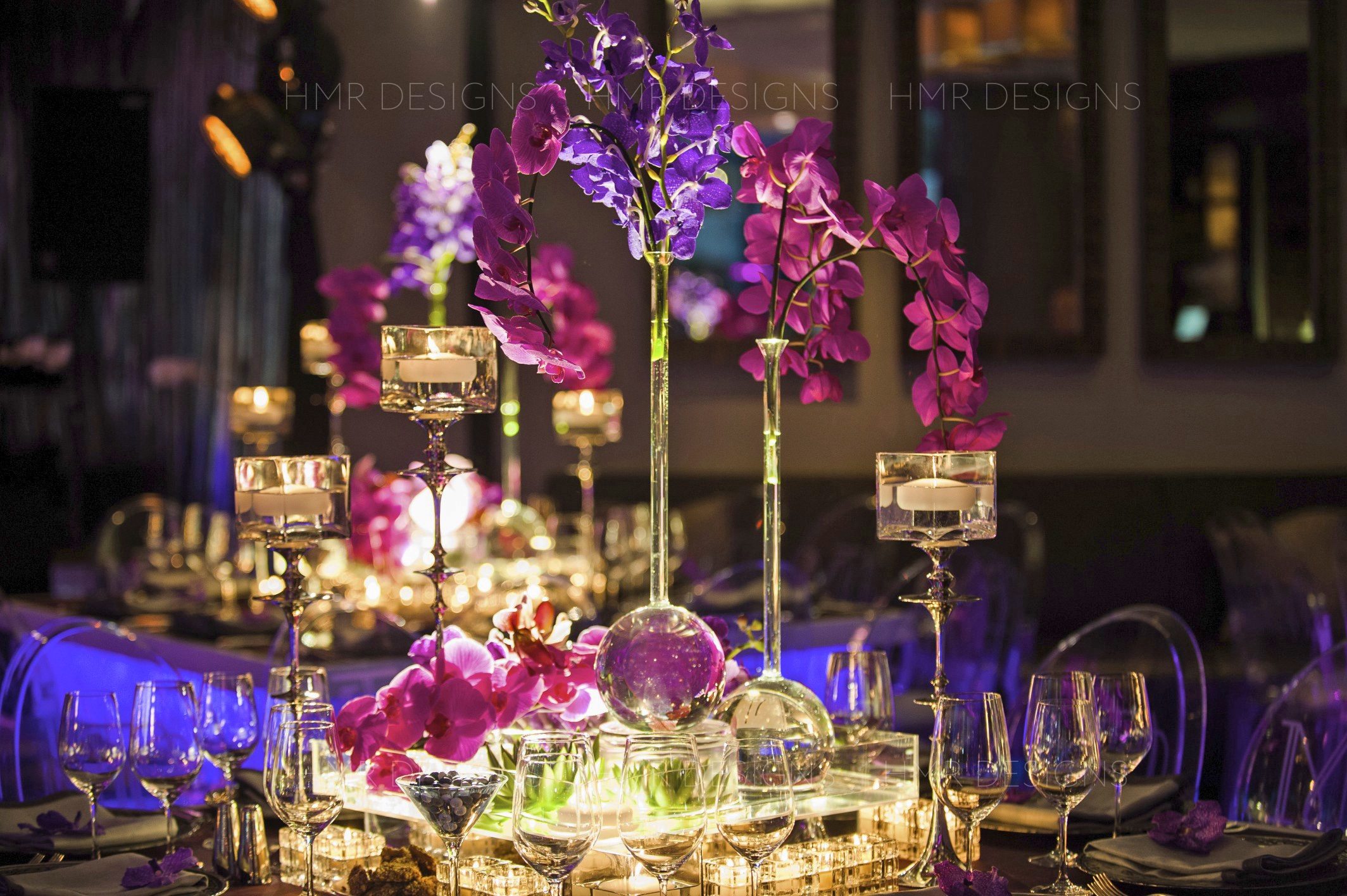Lush, modern centerpieces feature sleek candlelight and radiant magenta and purple orchids for a custom celebration at Trump International Hotel and Tower Chicago designed by HMR Designs