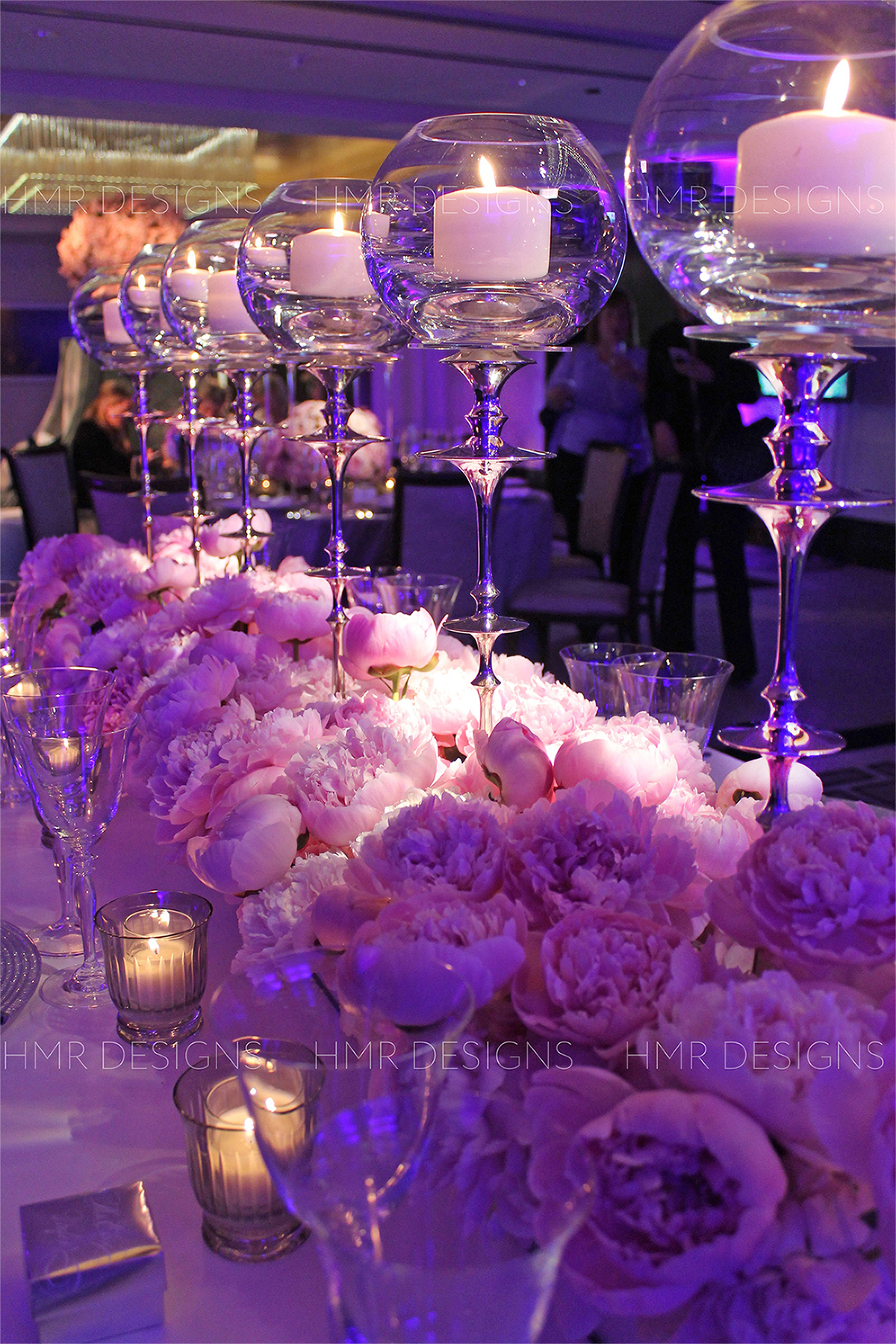 Lush, plentiful peonies mixed with sleek silver candlelight for centerpieces designed by HMR Designs for a luxury wedding at the Langham Chicago