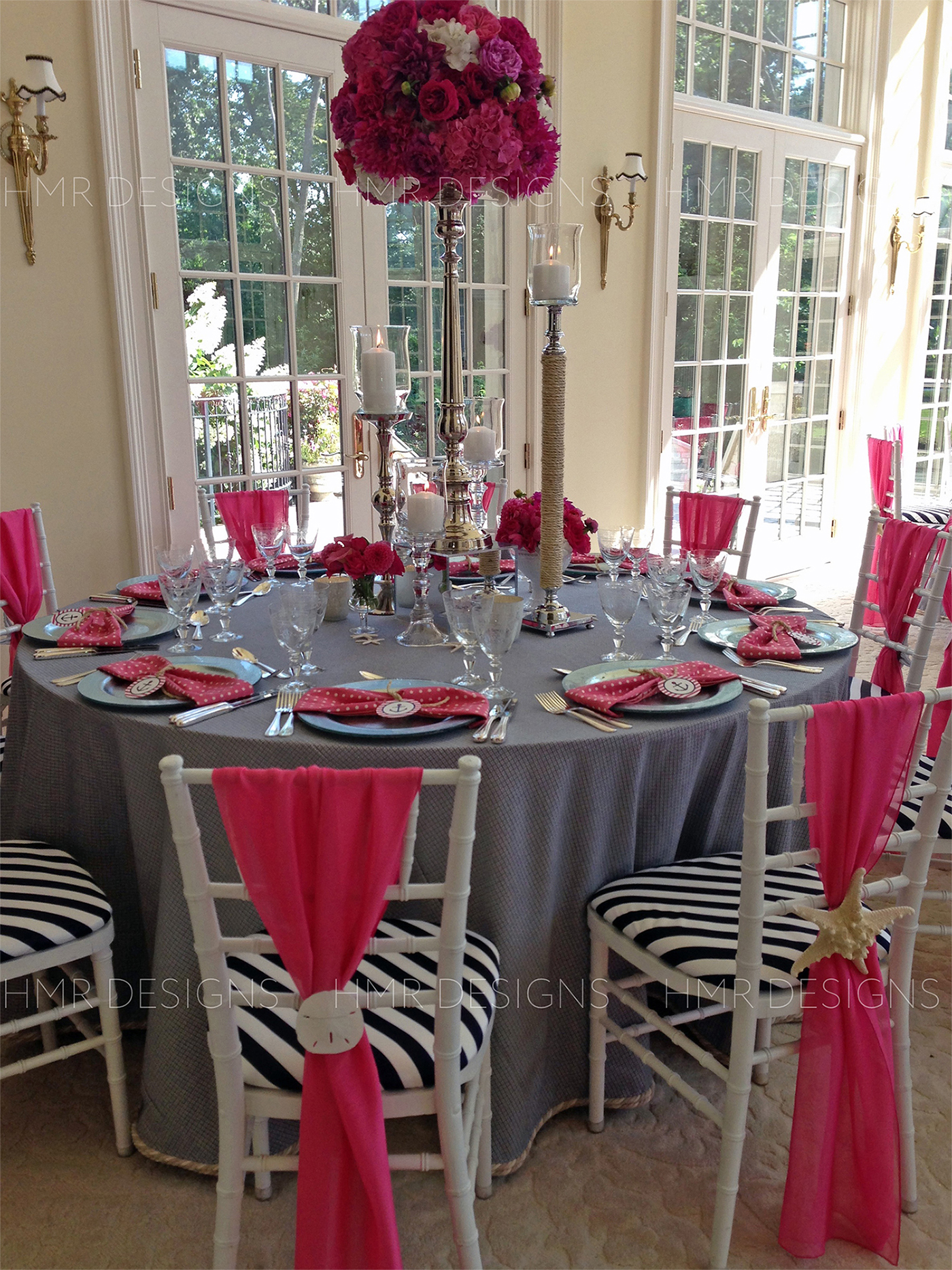 Nautical themed decor and sleek silver candlesticks adorn a table for a baby shower designed by HMR Designs