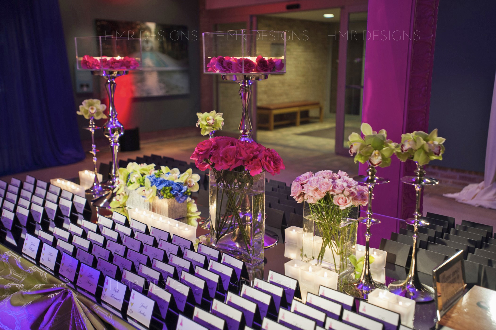 Sleek candlelight and lush bunches of pink floral adorn a placecard table at a custom Bat Mitzvah at Chicago Botanic Garden designed by HMR Designs