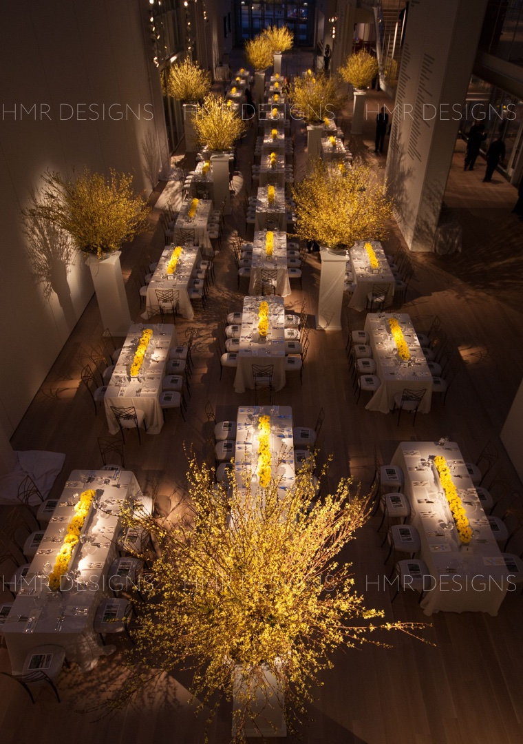 Bright yellow daffodil centerpieces and forsythia room focals line the Modern Wing of the Art Institute for a modern gala