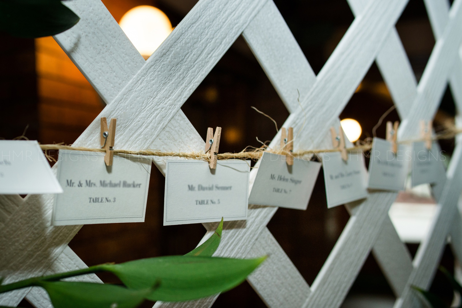 A lattice backdrop holds placecards at a spring wedding at Cafe Brauer by HMR Designs