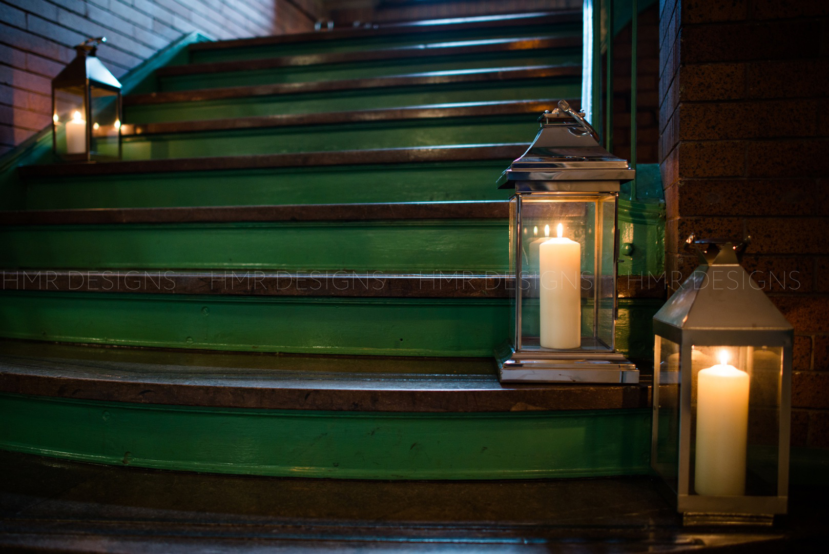 Iron lanterns line the stairs at Cafe Brauer for a spring wedding by HMR Designs