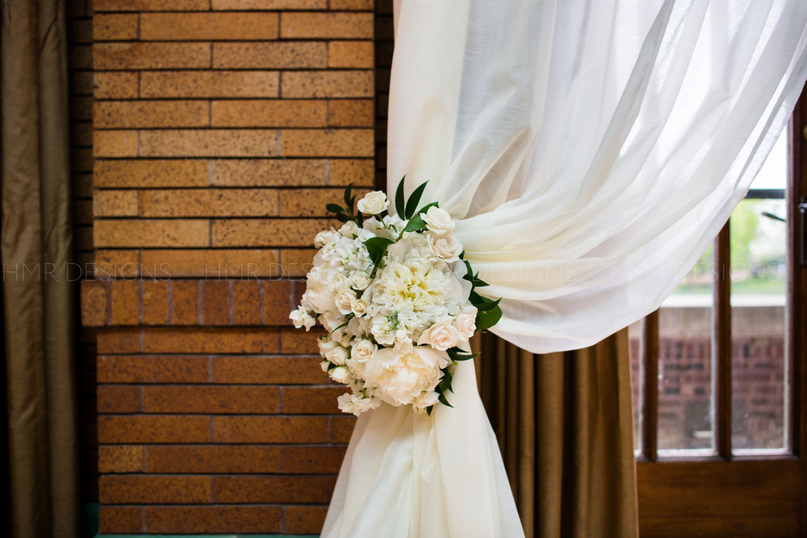 Drapes are tied back with lush spring floral at a spring wedding at Cafe Brauer in Chicago by HMR Designs