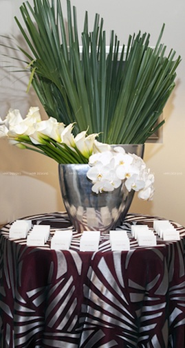 A chic place card piece with lilies, orchids, and palms by HMR Designs