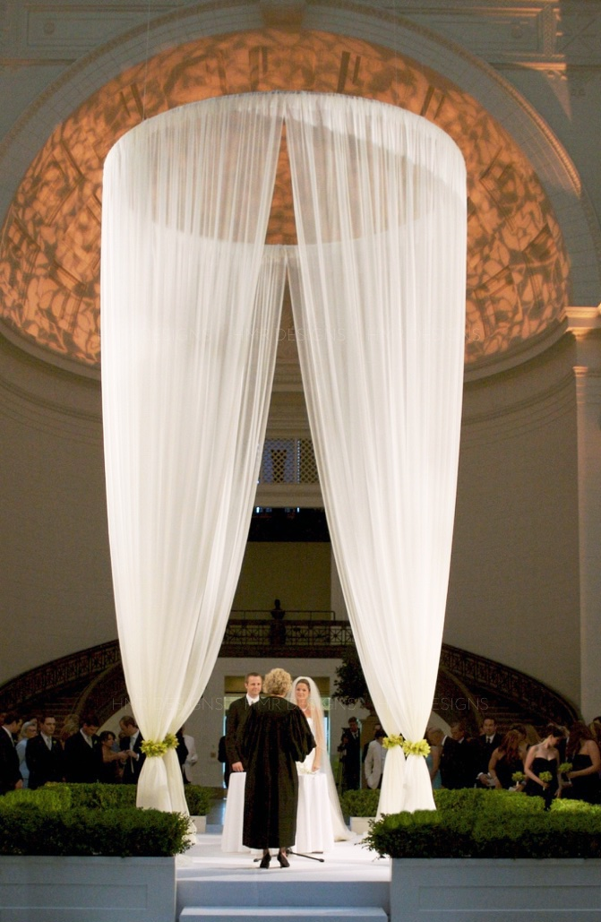 A custom fabric chuppah by HMR Designs reaches the vaulted ceiling of the Field Museum.