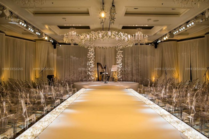 Ethereal and ivory: a custom built raised aisle is punctuated by paths of ivory petals, leading to an almost angelic floral chuppah.