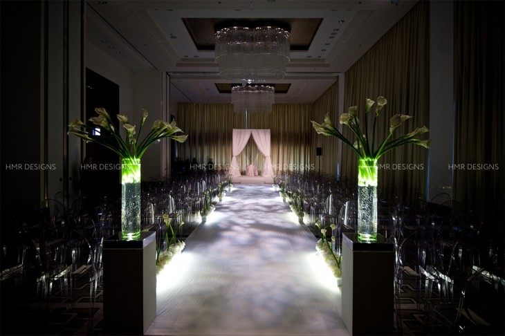 Stark calla lilies, illuminated glass, and low, lush aisle floral came together beautifully.