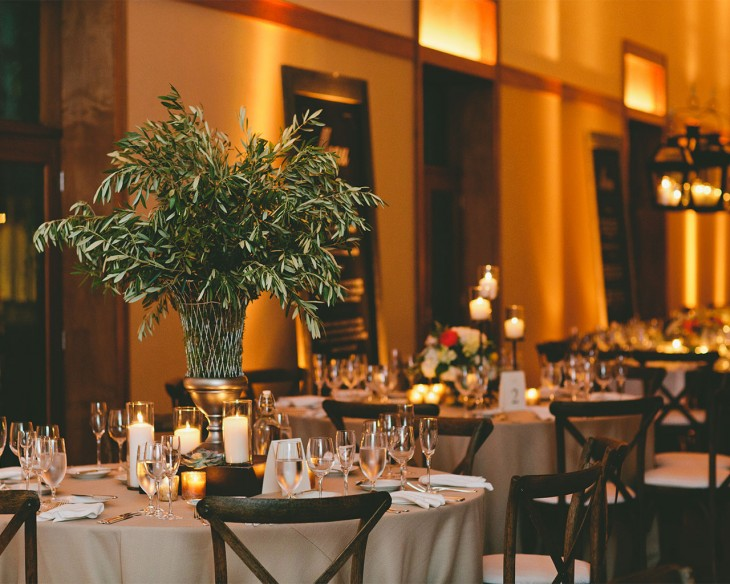 Olive branch foliage centerpieces are alternated with floral arrangements at a rustic Ivy Room wedding.