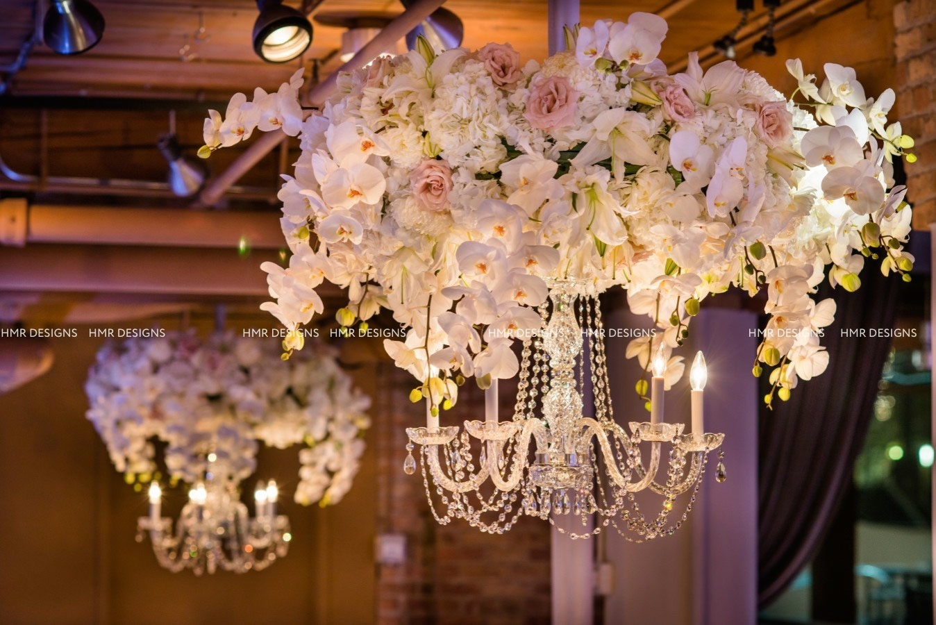 An orchid adorned chandelier at River East Arts Center by HMR Designs